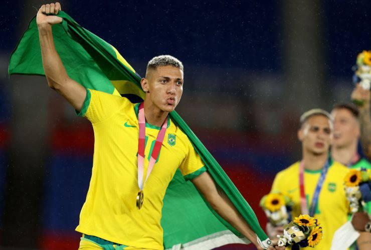 Richarlison esulta con bandiera del Brasile e medaglia d'oro al collo dopo la vittoria a Tokyo2020